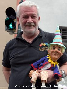 Klaus Marschall holds one of his puppets in his arm while standing before a pedestrian light in the shape of a puppet (picture-alliance/dpa/S. Puchner)
