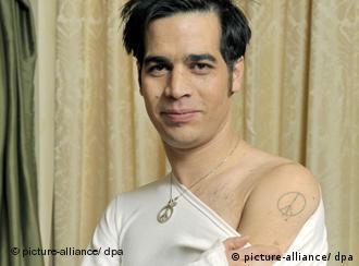 Aviv Geffen der die, mit einem Peace-Zeichen tätowierte, nackte Schulter zeigt