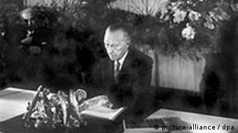 Председатель Парламентского совета Конрад Аденауэр подписывает Основной закон ФРГ