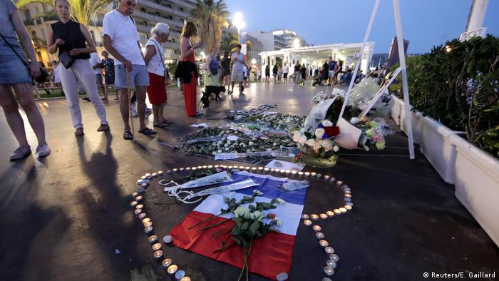 People look at candle tributes and flowers on the promenade boardwalk in Nice (Reuters/E. Gaillard)