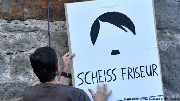 One of the protesters with a Lousy hairdresser placard.