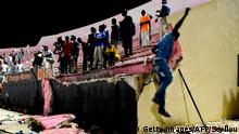 People look at the scene after a wall collapsed at Demba Diop stadium July 15, 2017 in Dakar after a football game between local teams Ouakam and Stade de Mbour. Eight people were killed during Senegal's football league final in Dakar on Saturday in a stampede that broke out following clashes at the end of the match, the official APS news agency said. The wall collapse adding many more to be injured. / AFP PHOTO / SEYLLOU (Photo credit should read SEYLLOU/AFP/Getty Images)