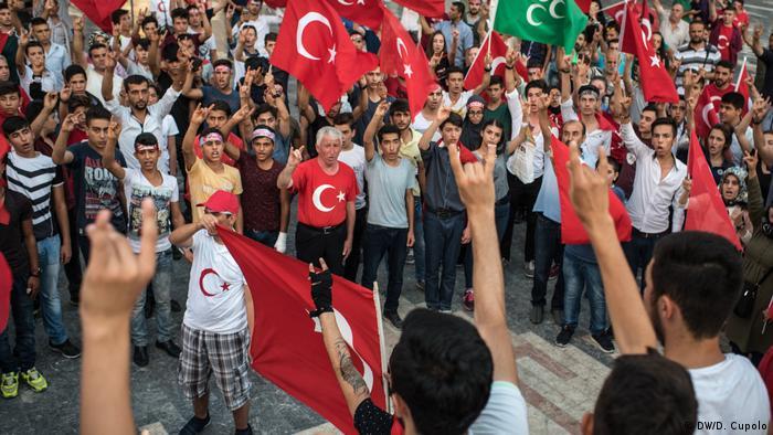Demonstranten mit türkischen Nationalsymbolen. Manche heben die Hand zum Wolfsgruß der rechtsextremen Partei der Nationalistischen Bewegung, genannt Graue Wölfe.