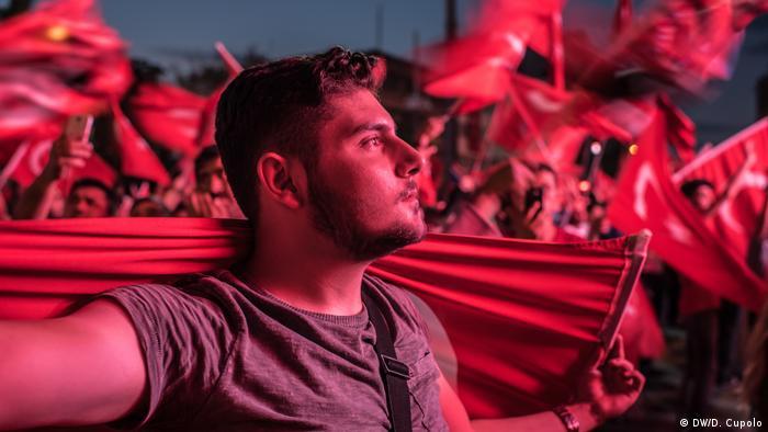 Demonstranten mit türkischen Flaggen in rotes Licht getaucht.