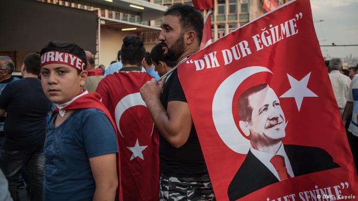 """Ein Teilnehmer der Veranstaltung trägt eine Flagge mit einem Erdogan-Porträt. """"Bleib stark, das Volk ist mit dir""""."""
