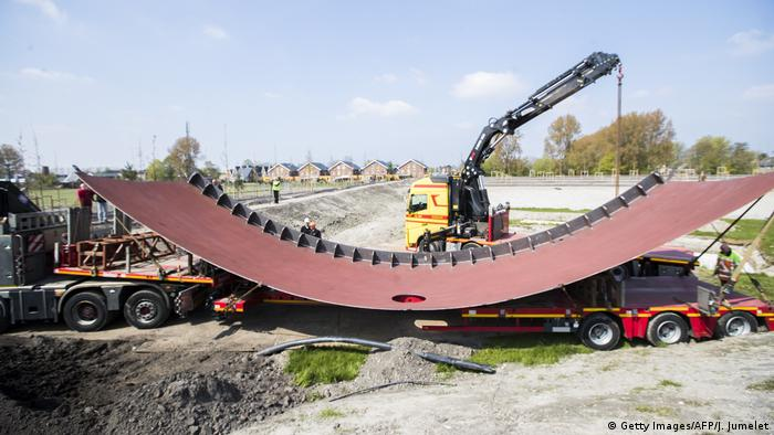 The steel wall of the memorial to the victims of flight MH17 is moved into place