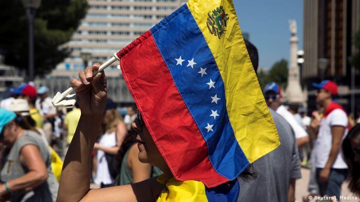 A woman holds a Venezuelan national flag