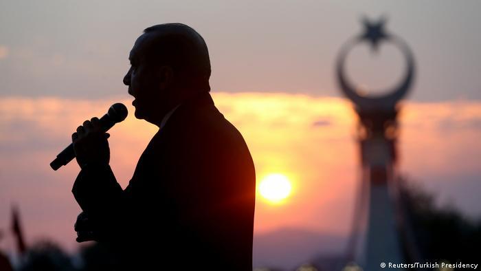 Silhueta do presidente turco, Recep Tayyip Erdogan, com pôr do sol e torre com crescente islâmica ao fundo