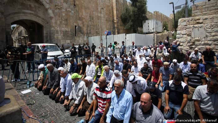 Palestinians perform prayer in front of the new security metal detectors