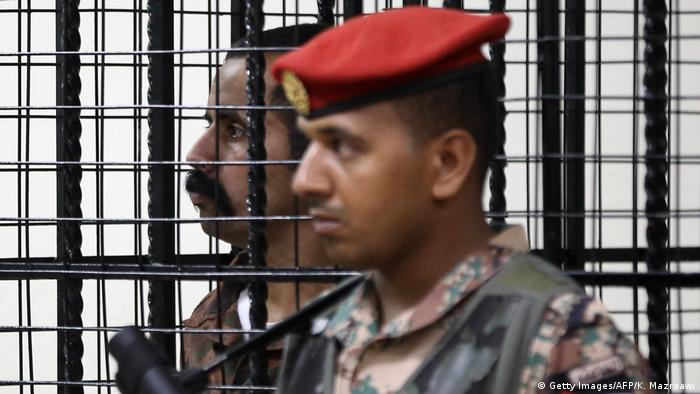 Jordanian soldier Maarik Al-Tawayha standing behind bars during his trial.