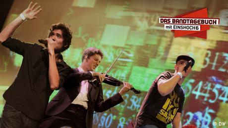 Mitglieder der Band Einshoch6 bei einem Konzert, oben rechts das Logo vom Bandtagebuch