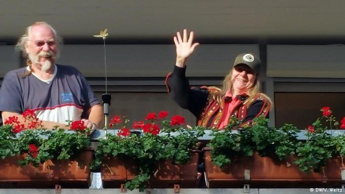 Чоловік і жінка на балконі, прикрашеному геранню
