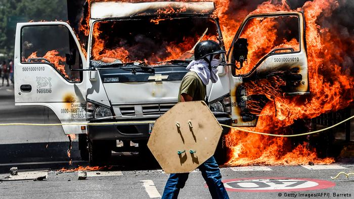 A protester walks in front of a van on fire