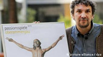 Christian Stueckl, holding a poster for the Passion Play