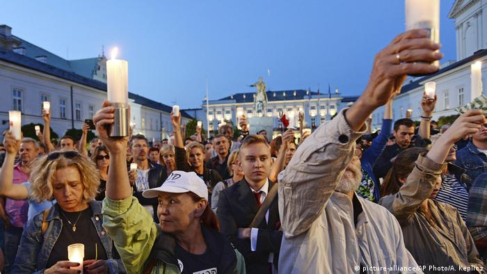 Poles holding up candles at protest in Warsaw