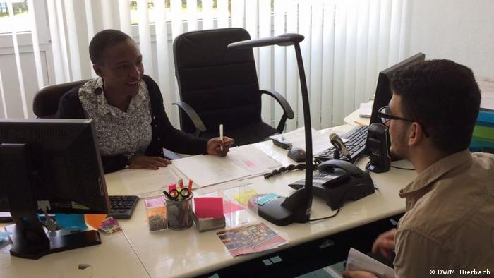 Yvonne Chipo Makopa talks with a young man from behind her desk