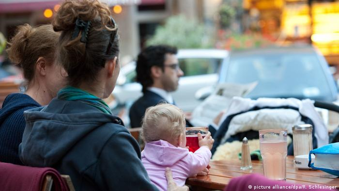 Two women sit with a child in an outdoor café