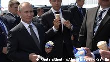 Russian President Vladimir Putin and Industry and Trade Minister Denis Manturov hold ice cream during a visit to the MAKS 2017 air show in Zhukovsky, outside Moscow, Russia, July 18, 2017. Sputnik/Alexei Nikolsky/Kremlin via REUTERS ATTENTION EDITORS - THIS IMAGE WAS PROVIDED BY A THIRD PARTY.