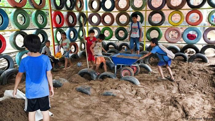 Children help move sand in a room with colorful tires for walls
