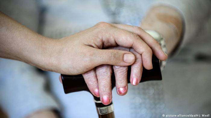 Hand of a younger carer on that of an old woman (picture-alliance/dpa/H-J. Wiedl)