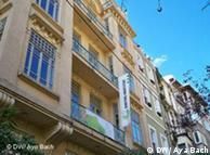 Die Zentrale des Goethe-Instituts Istanbul: Eine helle Altbau-Fassade unter blauem Himmel, davor die Fahne mit dem grünen Logo des Goethe-Instituts
