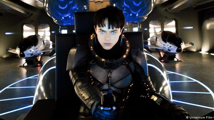 Filmszene aus Valerian - Die Stadt der tausend Planeten von Luc Besson mit einem Raumfahrer im Cockpit eines Raumschiffes (Universum Film)