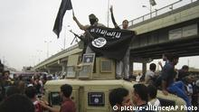 ARCHIV März 2014 FILE - In this Sunday, March 30, 2014, file photo, Islamic State group militants hold up their flag as they patrol in a commandeered Iraqi military vehicle in Fallujah, 40 miles (65 kilometers) west of Baghdad, Iraq. (AP Photo, File) |