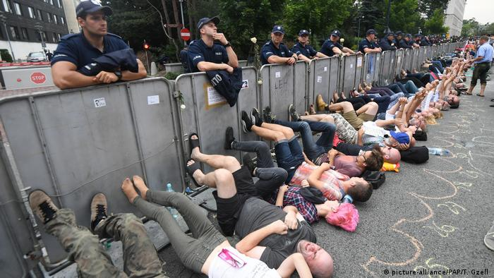People lay on the ground in a protest in front of the Sejm building in Warsaw