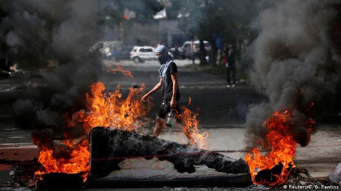 Manifestante caminha atrás de barricada em Caracas, em protesto contra Maduro em 20 de julho de 2017