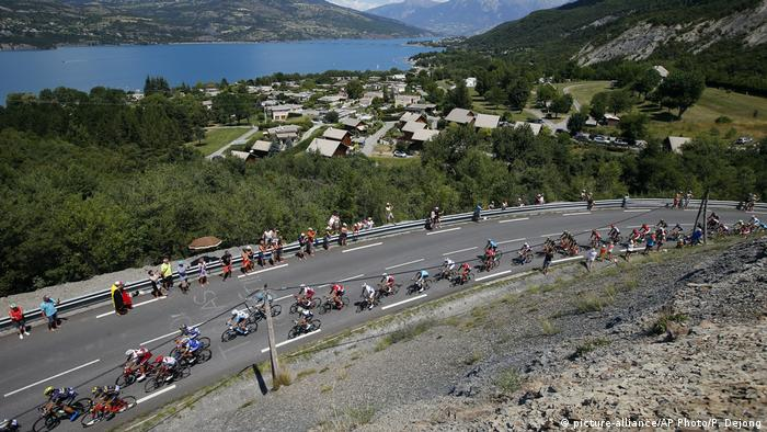 The pack rides next to Serre Poncon lake during the eighteenth stage of the Tour de France cycling race over 179.5 kilometers (111.5 miles) with start in Briancon and finish on Izoard pass, France, Thursday, July 20, 2017. (AP Photo/Peter Dejong) |