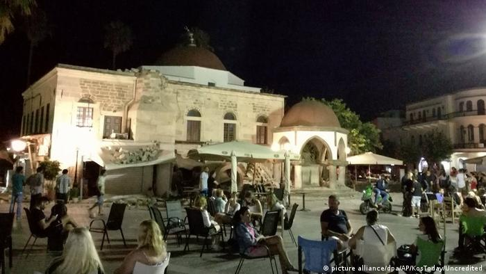 People sit at a square after the earthquake on Kos