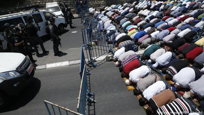 Muslim worshippers pray during traditional Friday prayers on a street outside the Lion Gate.