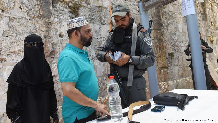 Israeli border police check documents of Palestinian Muslims at a newly installed metal detector