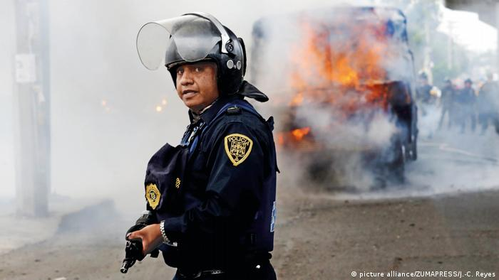 Policeman in front of burning bus