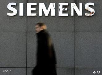 A man in a black coat walking past a Siemens logo