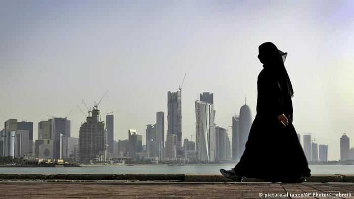 A veiled woman walks in front of the city skyline in Doha