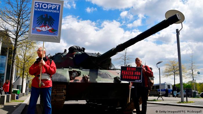 Activists stand in front of a tank and hold up signs reading stop exports of weapons to protest against plans of German military technology group Rheinmetall to built a tank factory in Turkey