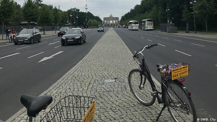 Bikes by a road in Berlin with the Brandenburg Gate in the distance (DW/B. Chy)