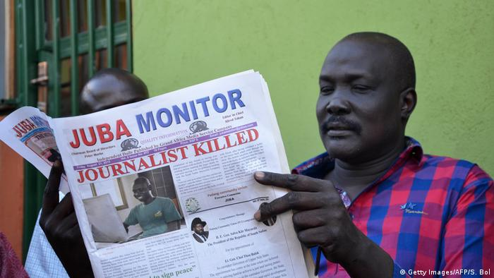 A man reading the South Sudanese newspaper 'Juba Monitor' with a frontpage article entitled 'Journalist killed'