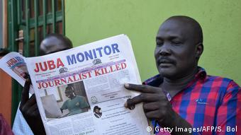 A man sits reading the Juba Monitor newspaper with the headline Journalist killed