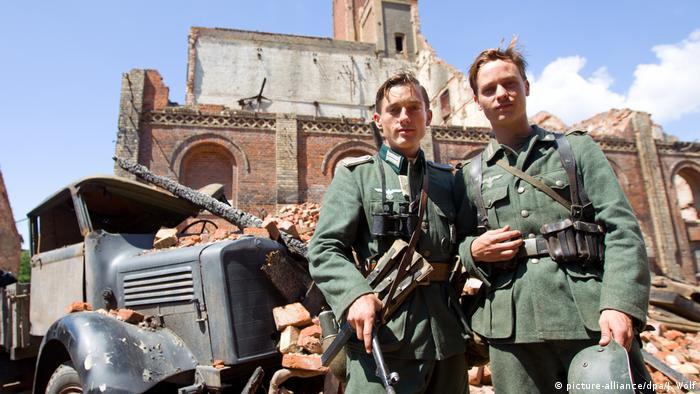 Filmszene aus der Serie - Unsere Mütter, unsere Väter mit 2 Soldaten vor Trümmerstadt und Auto (picture-alliance/dpa/J. Wolf)