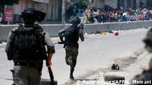Israeli security forces run towards Palestinian demonstrators during clashes at the Qalandiya checkpoint, between Ramallah and Jerusalem, in the occupied West Bank, on July 21, 2017, in support of the Al-Aqsa mosque compound after Israeli police barred men under 50 from entering the Old City of Jerusalem for Friday Muslim prayers. The ban came after Israeli ministers decided not to order the removal of metal detectors erected at entrances to the Al-Aqsa mosque compound, known to Jews as the Temple Mount, following an attack nearby a week ago that killed two policemen. / AFP PHOTO / ABBAS MOMANI (Photo credit should read ABBAS MOMANI/AFP/Getty Images)