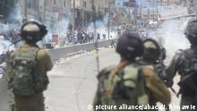 RAMALLAH, WEST BANK - JULY 21 : Israeli forces intervene to Palestinian demonstrators using tear gas as they stage a demonstration to protest Israeli violations and restrictions on Al Aqsa Mosque at Qalandiya checkpoint in Ramallah, West Bank on July 21, 2017. Israeli Government restricted entrance of under 50-year-old Palestinians to the the Al-Aqsa Mosque Compound and assembled metal detector gates. Qalandiya military checkpoint, located between East Jerusalem and West Bank. Issam Rimawi / Anadolu Agency |