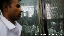 17.06.2017 *** A police officer stands guard as defendants accused of involvement in the 2015 assassination of Egypt's top prosecutor are seen in a cage in a courtroom, on the outskirts of Cairo, Egypt, June 17, 2017. Picture taken June 17, 2017. REUTERS/Amr Abdallah Dalsh