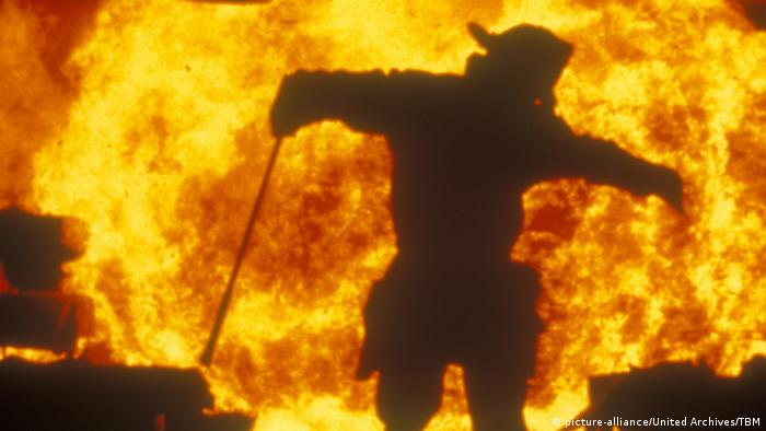 Man in protective gear including helmet and cane with a huge fire ablaze behind him.