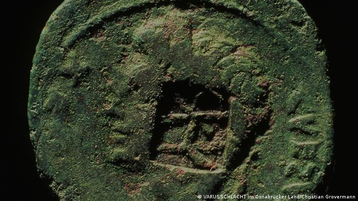 Centenas de moedas foram descobertas em Kalkriese, empilhadas – sinal de uma desgraça iminente, já que os soldados teriam tentado esconder seus tesouros antes da derrota. A moeda da foto mostra o selo de Quintílio Varo, o comandante romano da Germânia. Até agora, nenhuma das moedas foi identificada com data posterior a 9 d.C. – um sinal de que Kalkriese pode mesmo ter sido o local da batalha.