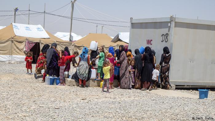 Women and children collect water in Salamiyah camp near Mosul