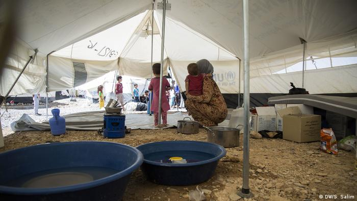 Hanan Mohammed and her children look from their tent out into Salamiyah camp