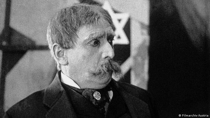 Filmszene aus Die Stadt ohne Juden mit einem Mann mit Schnurrbart (Filmarchiv Austria)