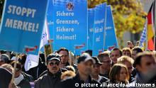 ARCHIV- Demonstranten nehmen am 17.10.2015 in Freilassing (Bayern) an einer Kundgebung teil und tragen Plakate der AfD mit der Aufschrift Sichere Grenzen, sichere Heimat! und Stoppt Merkel!. (zu dpa Bertelsmann-Stiftung stellt Populismus-Studie zur Bundestagswahl vor vom 24.07.2017) Foto: Aktivnews/dpa +++(c) dpa - Bildfunk+++   Verwendung weltweit